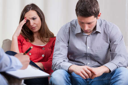 couples therapy: Couple talking about problems at psychotherapy, horizontal