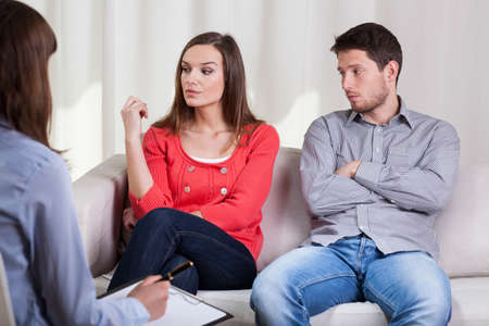 Sad marriage talking with female therapist, horizontal photo