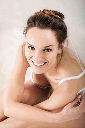 nude wife: Portrait of a sensual bride wearing white lingerie and white veil Stock Photo