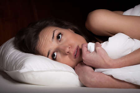 frightened: Young woman lying in bed and looking frightened at night