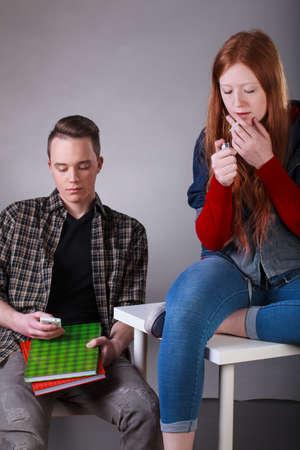 chica fumando: Vista vertical de unos adolescentes problemáticos que fuman el cigarrillo y mensajes de texto en el aula Foto de archivo