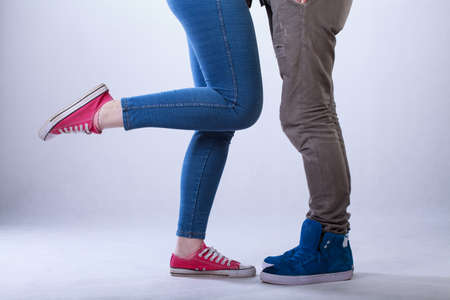 closeup on legs: Close-up of teenage couple legs on isolated grey background Stock Photo