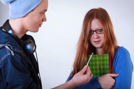 marihuana: Naughty boy mostrando cigarrillo de marihuana para calmar chica estudiante