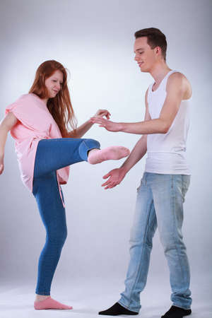 brother sister fight: Redhead teenage girl kicking a boy, vertical Stock Photo