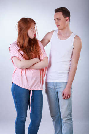 offend: Offended teenage girl with her boyfriend on isolated grey background