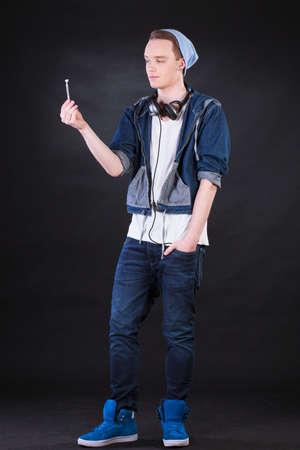 naughty boy: Naughty teenage boy holding marijuana joint on isolated black  Stock Photo
