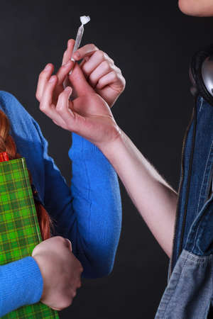 narcotics: Close-up of drug dealer selling narcotics to young student girl Stock Photo