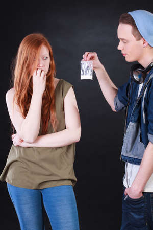 drug deals: Drug dealer and addicted teenage girl on isolated black  Stock Photo