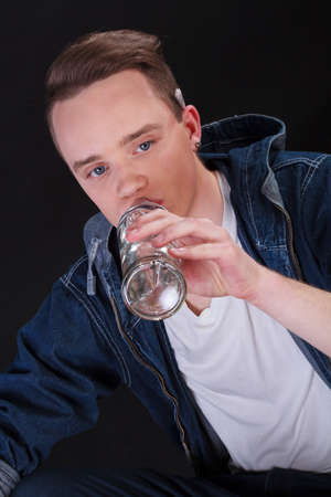 Portrait of a teenage boy drinking alcohol on black isolated  photo
