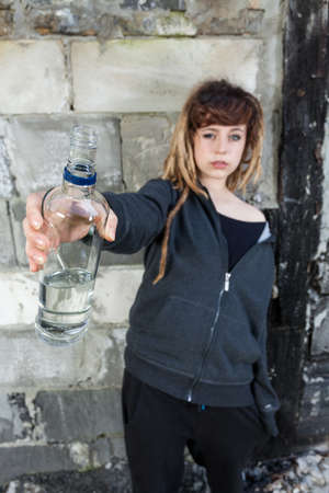 vandalize: Young girl with bottle of vodka, vertical