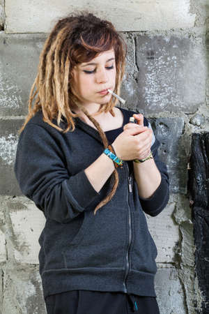 youth crime: A girl during smoking after school, vertical
