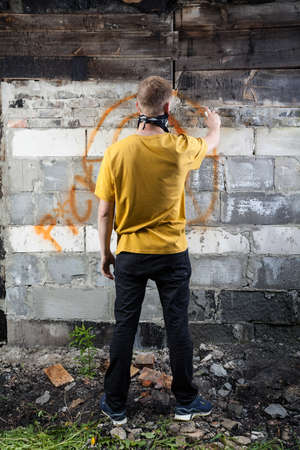 vandalize: Vertical view of male hooligan painting graffiti
