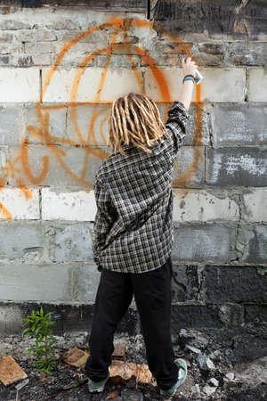 vandalize: Hooligan painting graffiti on the building, vertical