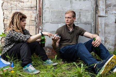 joven fumando: Un par de amigos que beben la cerveza después de la escuela