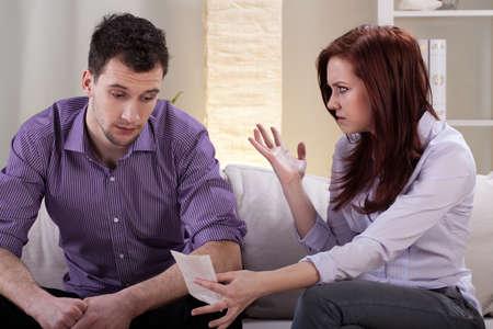 Femme en colère montrant factures à son mari Banque d'images