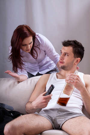 lazybones: Lazy man drinking whiskey and watching tv Stock Photo