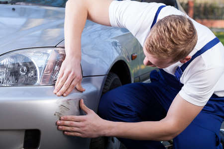Mechanic in uniform assess the damage on the car Stock Photo