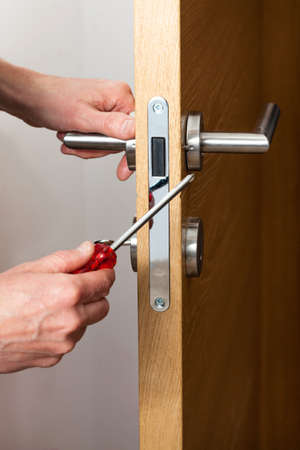 Hands repairing a door lock with a screwdriver