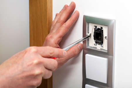 Hands with screwdriver repairing a light switch photo