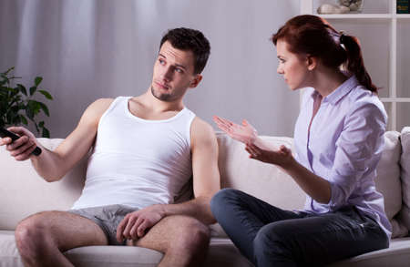 Lazy man and angry woman at home Stock Photo