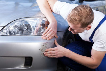 A man trying to fix a scratch on a car body Standard-Bild
