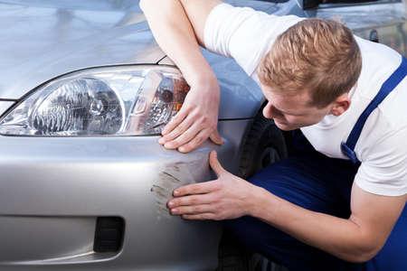 Een man probeert een kras op te lossen op een auto lichaam Stockfoto