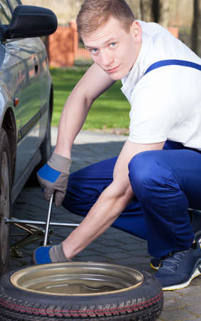 professionalist: A handsome professional wearing overalls repairing a car tire Stock Photo
