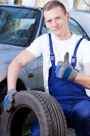 professionalist: A young mechanic with a tire and his thumb up