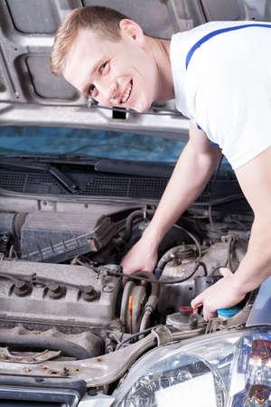 mechanic in uniform checks a car engine photo