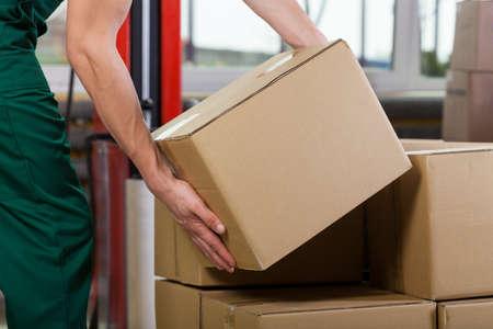 lifting: Handen van magazijnmedewerker tillen doos, horizontale