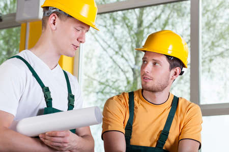Two young men in overalls and hardhat talking during work photo