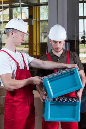 Production workers in protective workwear during job in factory