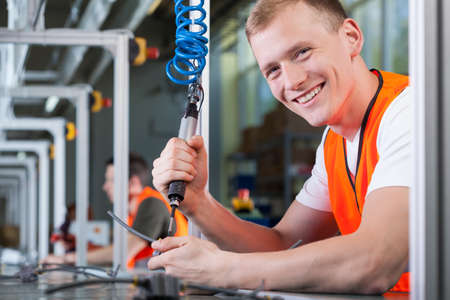 line up: Close-up of a young smiling man working on the production line Stock Photo