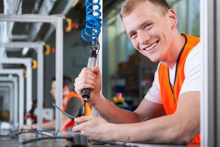 Primer plano de un hombre sonriente joven que trabaja en la línea de producción
