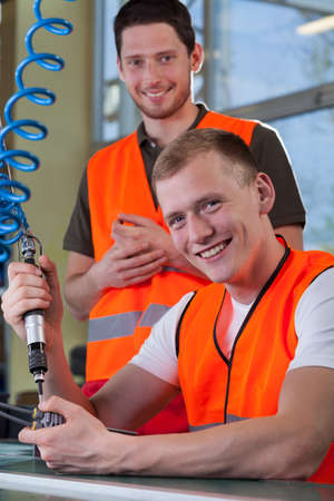 collaborators: Portrait of a smiling collaborators from factory during production process Stock Photo