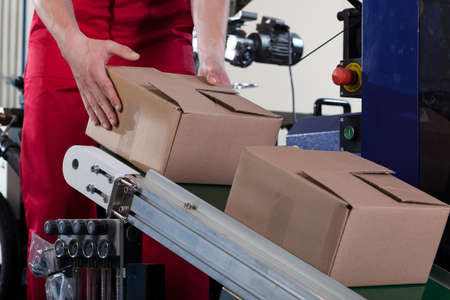 storekeeper: Close-up of worker putting a box on conveyor belt for shipping Stock Photo