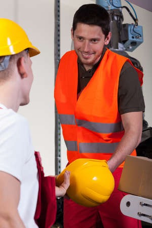 collaborator: Factory worker giving his collaborator hardhat, vertical