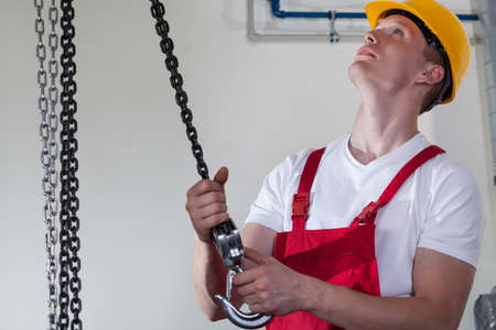 Man in overalls and hardhat using lifting hook at work