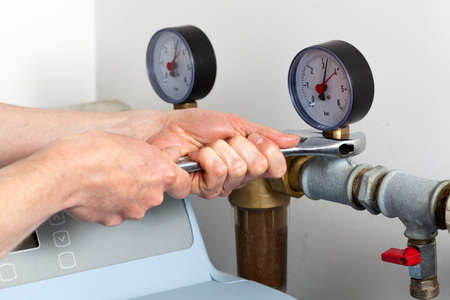 Man hands repairing pressure gauge and valve photo