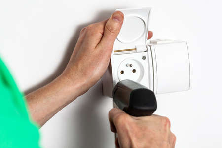 Hands with drill tightening a socket into a wall photo