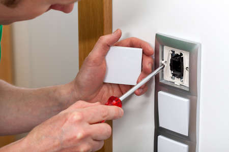 Man with screwdriver fixing the light switch photo