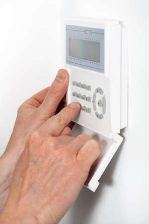 Hands entering a code to burglar alarm photo