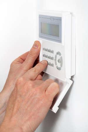burglar protection: Hands entering a code to burglar alarm
