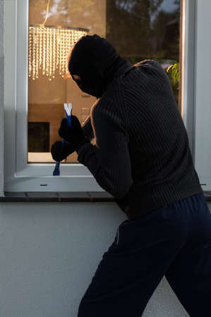 Burglar trying to open a window with a crowbar Stock Photo