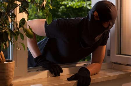 開いている窓から家の中に泥棒がピークします。