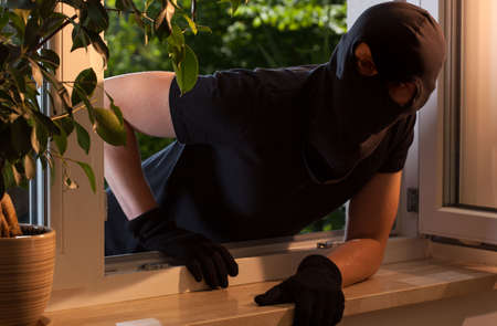 Inbreker gluurt naar binnen door een open raam Stockfoto