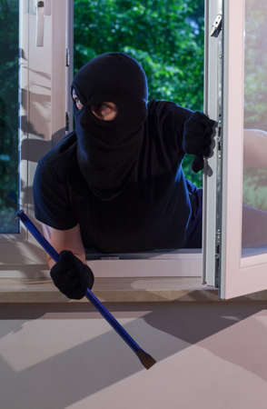 Burglar with crowbar in his hand looks around the apartment