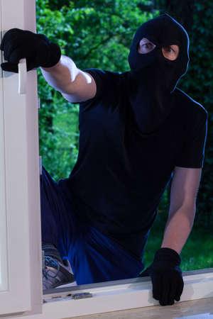 enters: A burglar enters the house through the window Stock Photo