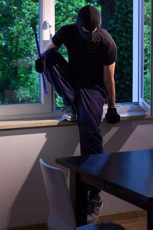 ladron: Ladrón entra a través de la ventana de la casa de alguien Foto de archivo