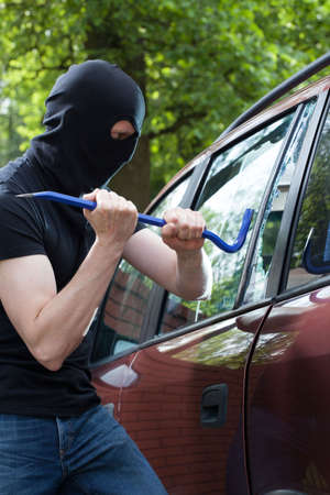 A thief with crowbar breaking into a car photo